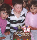 The children blow out the candles on the cake to celebrate our 60th birthday as a kindergarten.